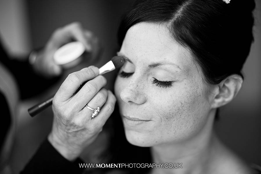 Wedding makeup being applied to bride in black and white photo