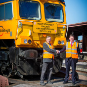 Train workers shake hands in front of a train of the West Somerset Railway