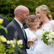 Bride laughin with a guest in the garden at Gants Mill