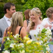 Bride chatting to a guest in the garden at Gants Mill