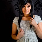 Pretty girl with black hair standing against black patterned background