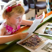 Little girl looking at old photos