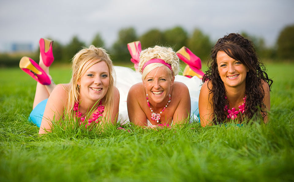 Bride lying in the grass with her bridesmaids