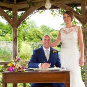 Bride and groom signing the register in the gazebo at Gants Mill