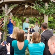 Bride and groom under a gazebo at Gants Mill with guests taking photos