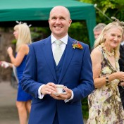 Groom smiling whilst holding teaccup at his wedding at Gants Mill