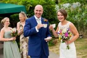 Bride and groom smiling with teacups in their hands at their wedding at Gants Mill