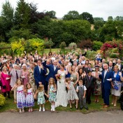 Bride and groom and all guests at their wedding in a group shot of the gardens of Gants Mill