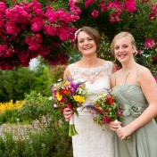 Bride posing with bridesmaid for photo in front of pink flowers at Gants Mill