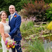 A bride and groom posing for a photograph in the attractive gardens at Gants Mill