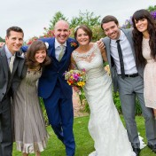A bride and groom posing for a photo with close friends at their wedding at Gants Mill