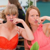 Two young attractive girls hold a fun temporary tattoo moustache to their face at a wedding at Gants Mill