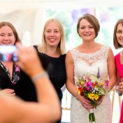A bride poses for a photo with her guests at a wedding at Gants Mill