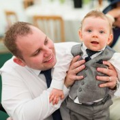 A little boy held up by his father at a wedding at Gants Mill