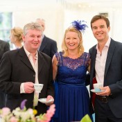 Guests smiling for a photo with tea cups in hand at a wedding at Gants Mill