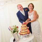 A bride and groom cut their cake at their wedding at Gants Mill