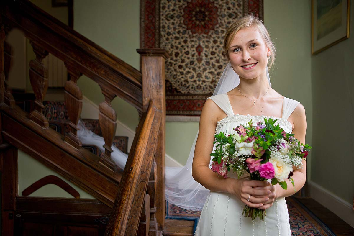 Pretty young bride stood on wooden staircase with bouquet of flowers