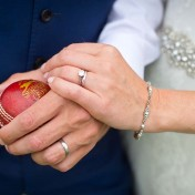 Newlyweds holding hands with cricket ball at Somerset County Cricket Ground