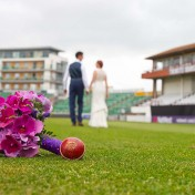 Bouquet on the pitch of Somerset County Cricket Ground with couple walking away
