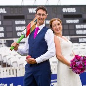 Newly weds in front of scoreboard at Somerset County Cricket Ground