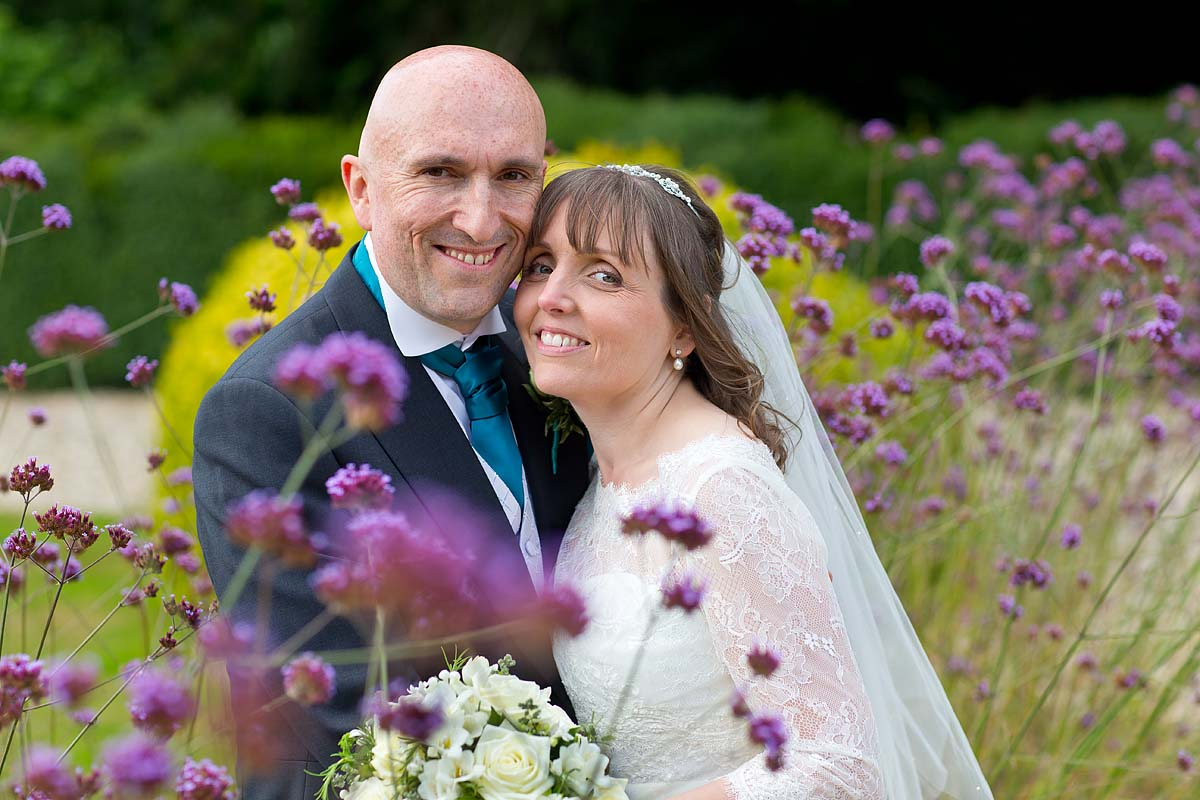 Romantic photo of bride and groom amongst the garden flowers at Dillington House