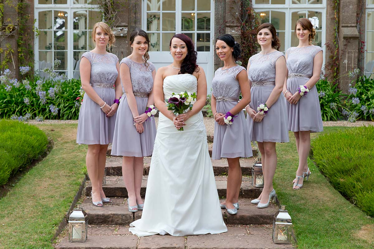 A bride with her bridesmaids in violet dresses stood on steps at St Audries park wedding venue