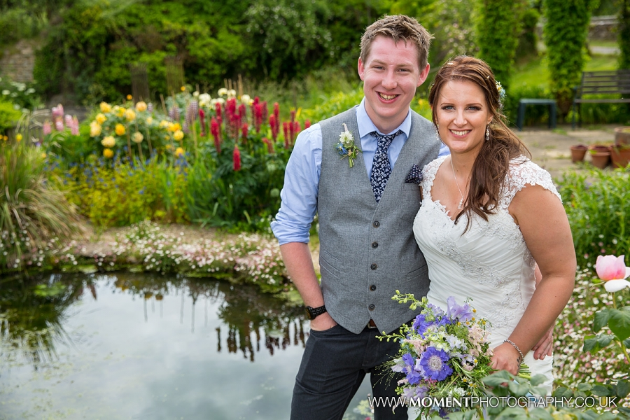 Bride and groom by the pond of the gardens at Gants Mill