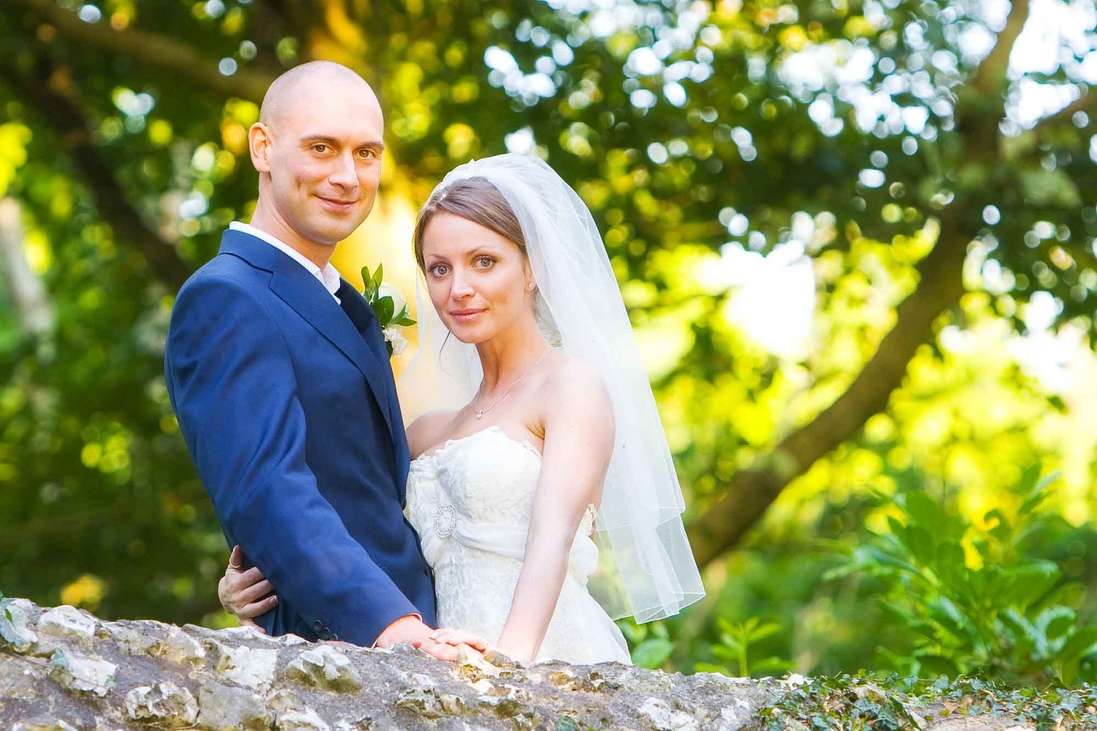 Colourful photo of attractive couple standing on a stone bridge at Lawrence Castle in Devon
