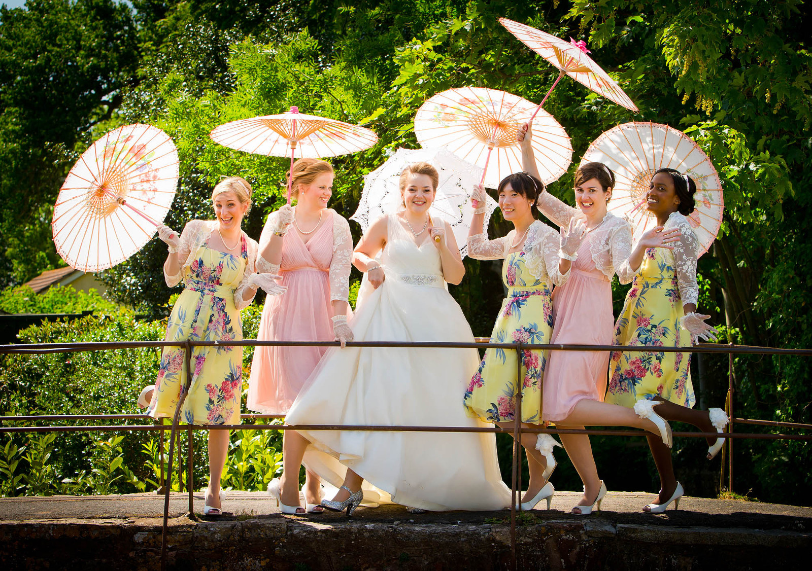 bride and bridesmaids backlit standing on bridge with parasols