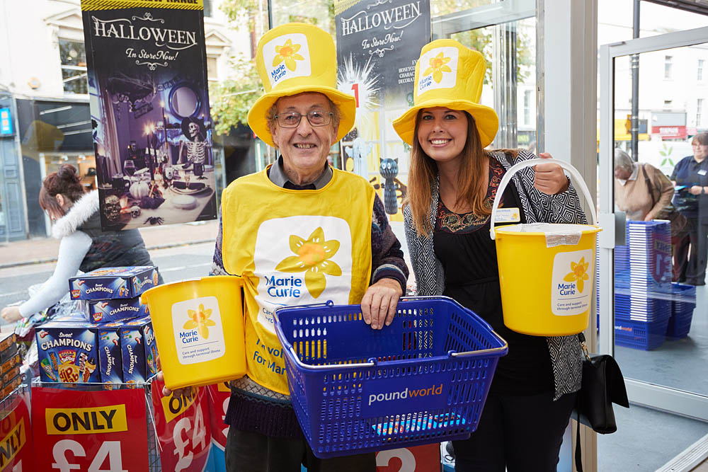 Two Marie Curie charity volunteers wearing big yellow hats and a yellow vest hold yellow collection buckets and a Poundworld shopping basket as they collect donations