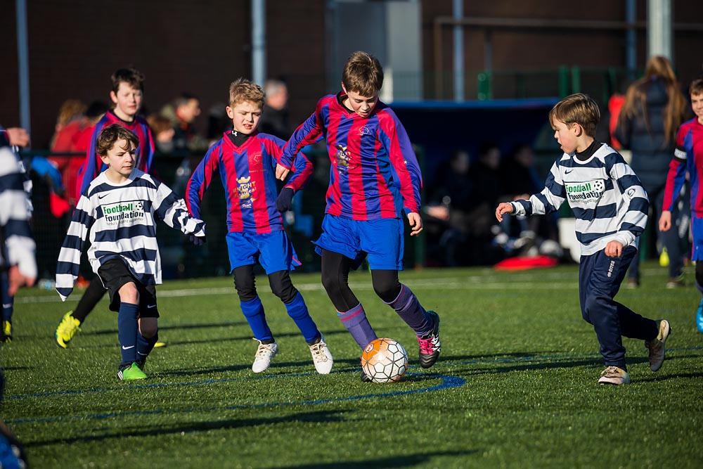 Junior boys competing playing football at Bridgwater College Academy tournaments