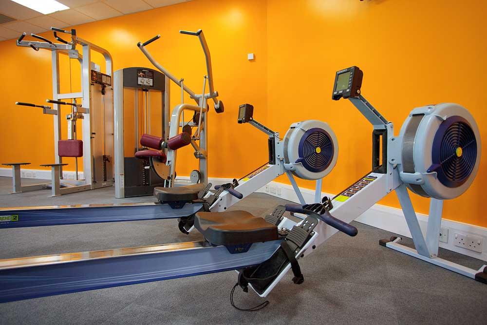 1610 gym equipment with bright orange walls behind