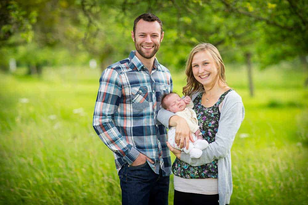 Young couple holding their baby stood smiling for a photo in front of summery green grass background