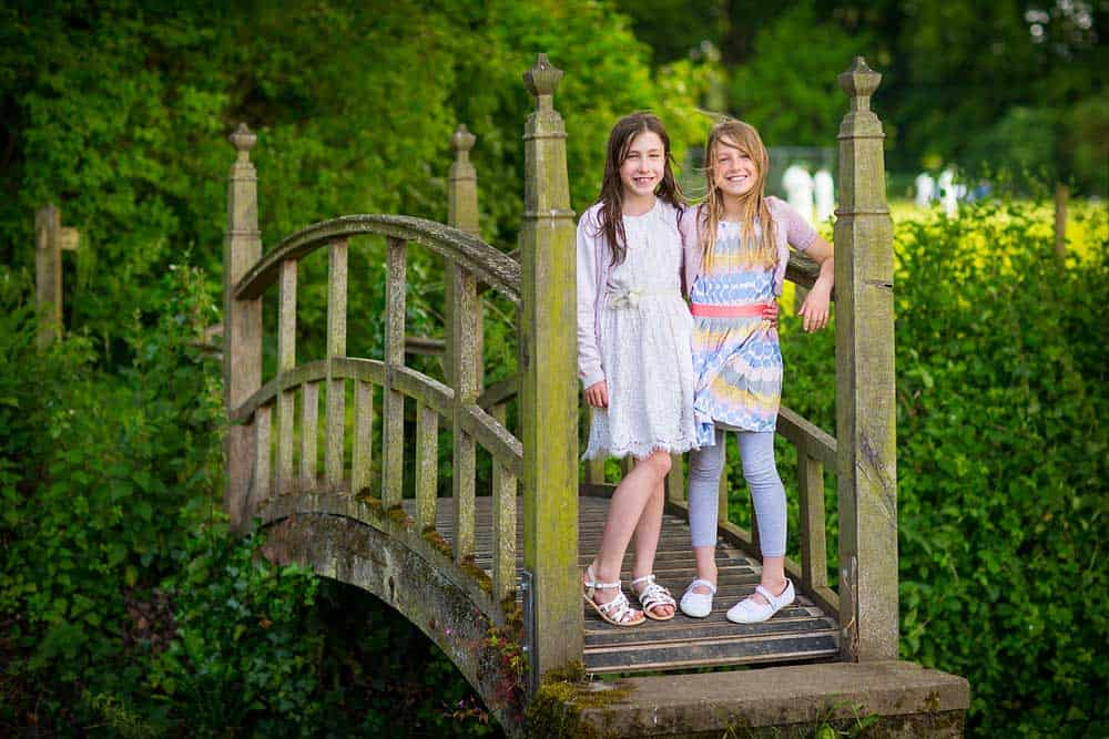 Two young girls stand next to each other on a beautiful old arched wooden bridge in the countryside