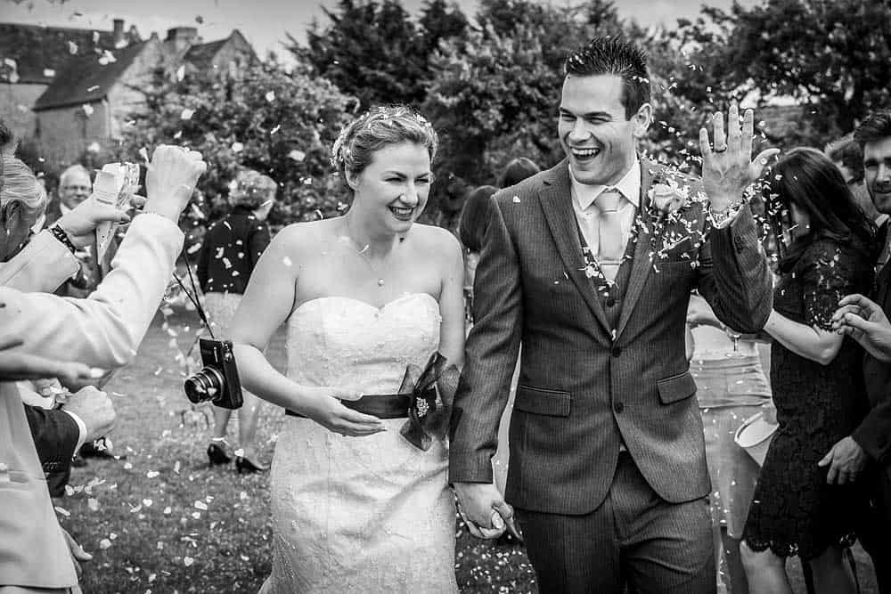 A black and white photo of a newly married couple laughing as they walk excitedly through a shower of confetti at their Somerset wedding