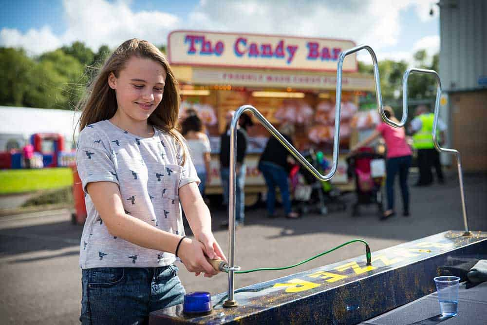 A young girl at a funfair tries her skill moving a hoop around the electric buzzer test game