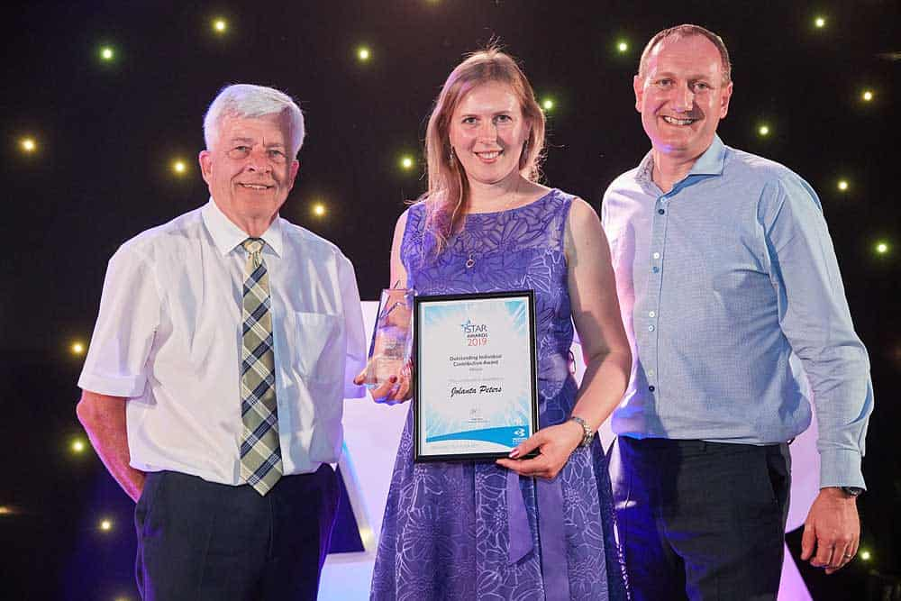 A young woman in a purple dress holds an award and a picture framed certificate during the awards ceremony at the star awards at Bridgwater and Taunton College