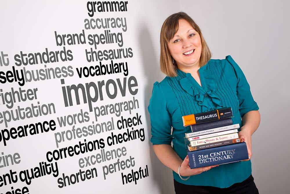 A young brunette women stands holding a pile of books next to a wall of words for a business profile photo