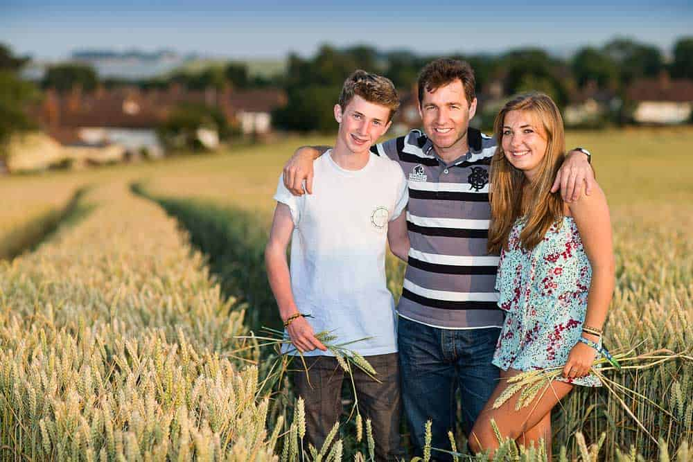A father stands with his teenage children in a cornfield in Cannington for a photo