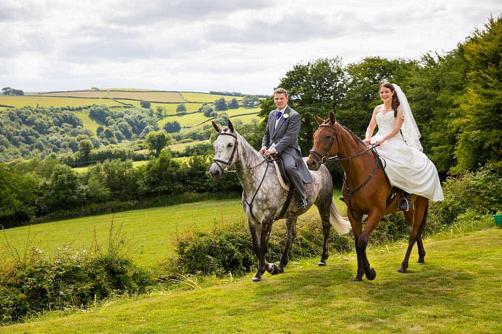 A bride and groom sit on horseback riding along the beautiful green fields in the Somerset countryside