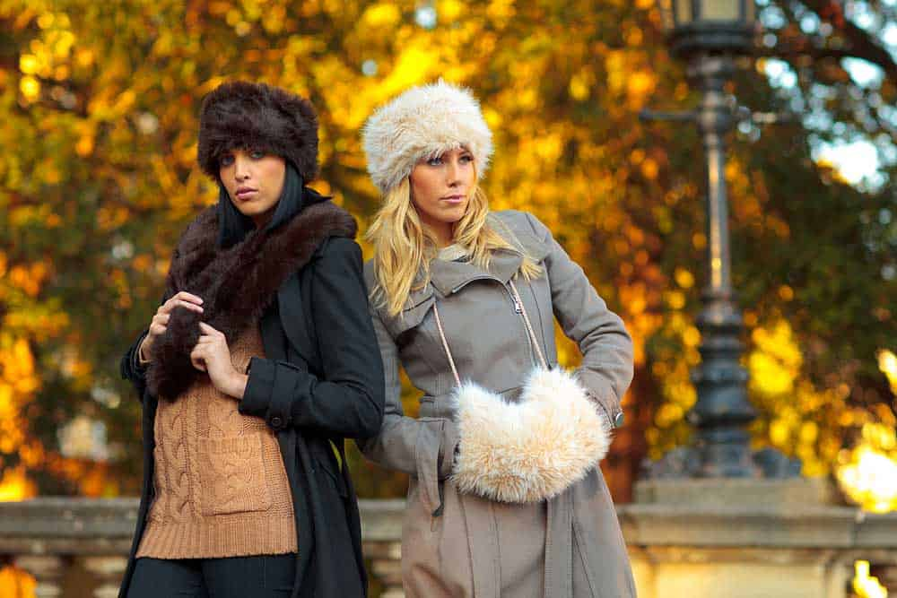 Young women modelling faux fur fashion products in front of a golden tree in Bristol