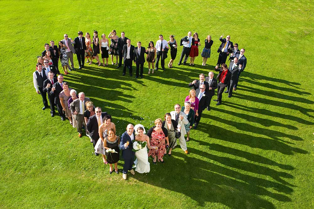 Looking down at a group of wedding guests in a heart shape on a large area of green grass at Lawrence Castle in Exeter
