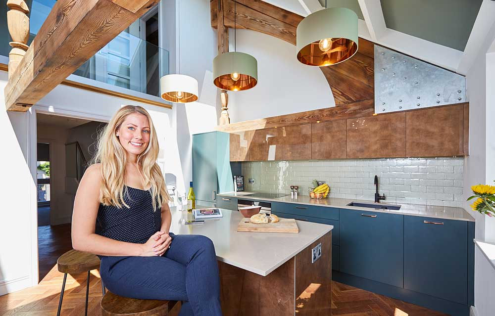 Beautiful young blonde lady sat in a luxurious modern kitchen with copper colours