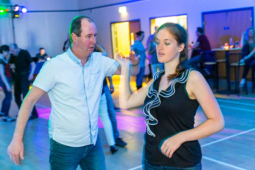 Pretty young lady jive dancing with a balding man in a room with colourful lighting