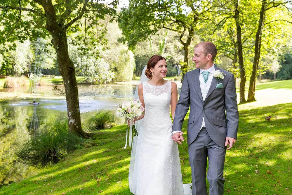 A bride and groom walk in beautiful dappled light next to a lake at the wedding venue Lakeview Manor in Honiton