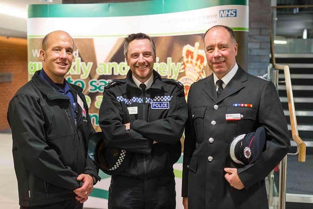 Three senior men who work for the emergency services stand for a photo at a conference at the Macmillan Theatre in Bridgwater