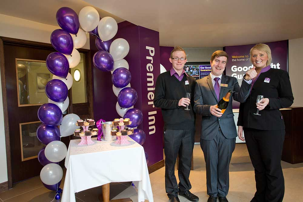 Staff of Premier Inn celebrating with a glass of champagne at the opening of their new hotel in Glastonbury
