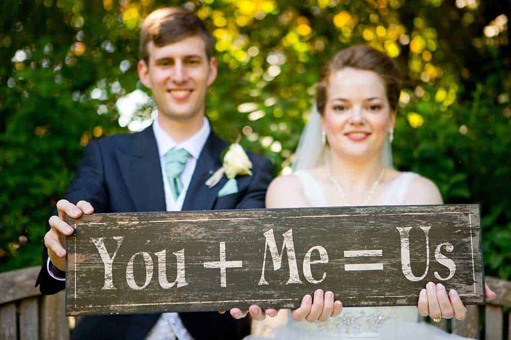 Bride and groom out of focus holding sign in front of them reading you and me equals us