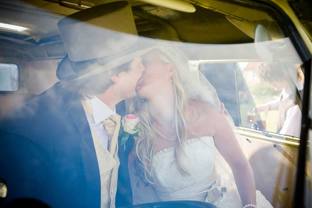 Groom wearing a top hat kissing his pretty blonde bride inside VW camper