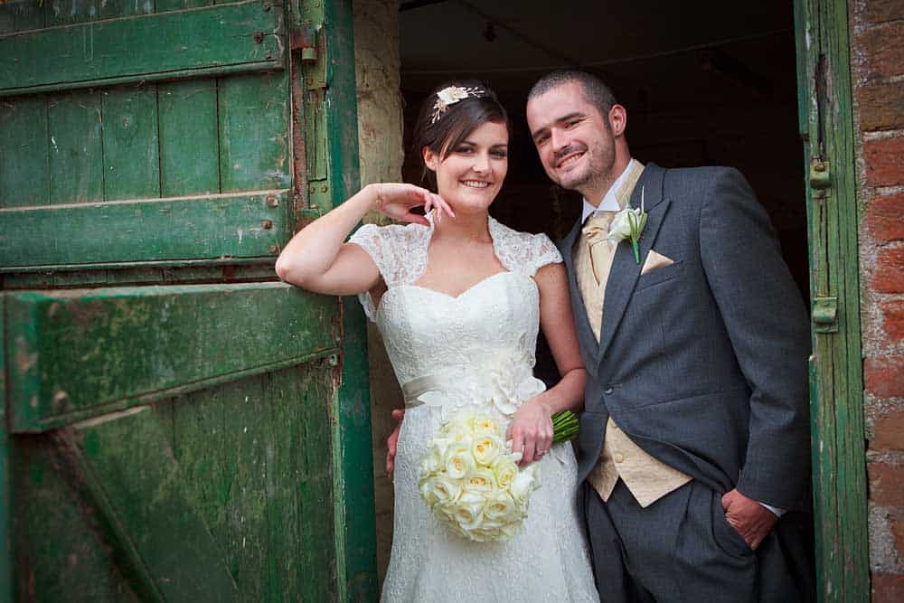 Bride stood in barn doorway resting her elbow on the door next to her groom on their wedding day in Somerset